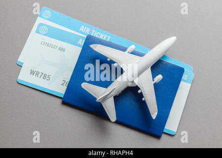 Tickets for plane and passport with model of passenger plane on gray background. - Stock Photo