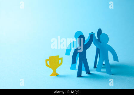 Successful business team winner holds gold cup in his hands. Team building. Leader and Workers Reach the Goal. Copy space for text