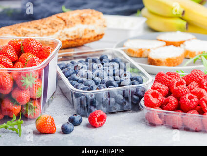 Plastic tray containers of fresh organic healthy beries and bread for fruit sandwiches. Blueberries, strawberries, bananas and raspberries on stone ki - Stock Photo