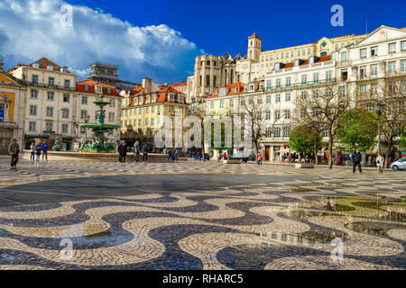 People walk in Dom Pedro IV square, also called Rossio, in Lisbon, Portugal - Stock Photo