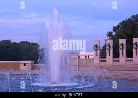 Fountain of World War II Memorial and brightly lit Lincoln Memorial on horizon at sunrise, Washington DC, USA. Sunrise on National Mall in US capital. - Stock Photo