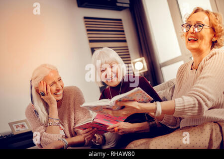 Joyful delighted woman spending time with her friends - Stock Photo