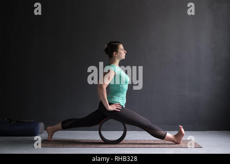 Young woman doing yoga or pilates exercise. Splits, hanumanasana using wheel - Stock Photo