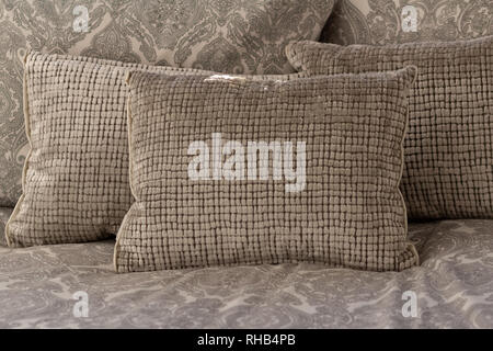 Pastel color, white and light grey cushions or pillows setting on bed - Stock Photo