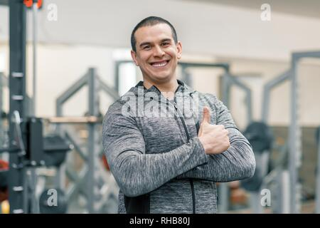 Portrait of muscular sporty smiling man showing thumbs up in gym, handsome trainer looking at the camera. - Stock Photo