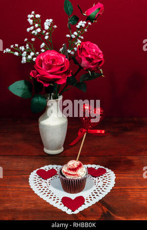 Beautiful pink roses in a vase accented with Baby's Breath flowers, heart shaped white dollie with a decorated cup cake with a heart on a pick. - Stock Photo