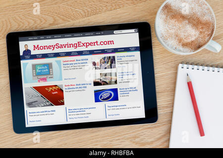 The MoneySavingExpert website features on an iPad tablet device which rests on a wooden table beside a notepad (Editorial use only). - Stock Photo