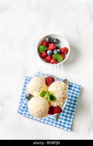 Topv view of vanilla ice cream in a bowl with berries on white background - Stock Photo