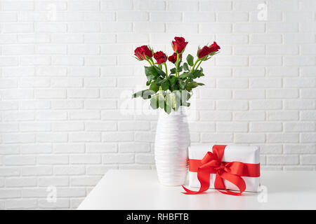 Red roses in white vase next to a gift box with red ribbon against white brocks wall - Stock Photo