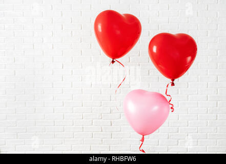 Valentines Day composition with red ballons on the left side against white bricks wall. Copy space - Stock Photo