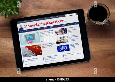 The website of MoneySavingExpert is seen on an iPad tablet, on a wooden table along with an espresso coffee and a house plant (Editorial use only). - Stock Photo
