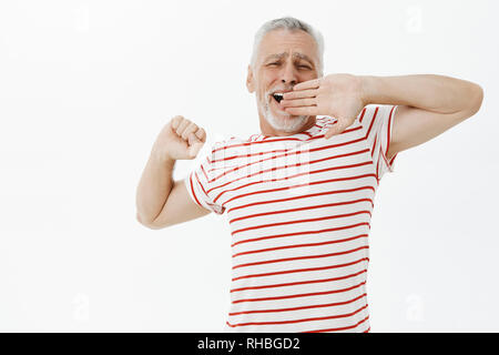 Old male pensioner feeling lazy today. Carefree relaxed handsome senior man with beard and grey hair in striped t-shirt stretching and yawning - Stock Photo