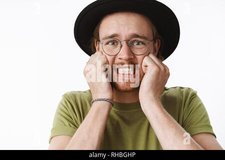Close-up shot of panicking, freaked out intense young guy clenching teeth standing shocked and anxious holding hands on cheeks and frowning being in - Stock Photo
