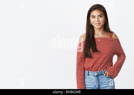 Friendly-looking stylish young indian teenage girl in striped blouse and jeans standing against gray background smiling shy at camera as holding one - Stock Photo