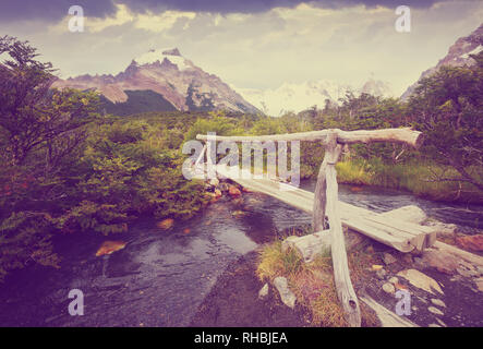Bridge over small river on trail at foot of mountains Fitz Roy and Cerro Torre, Andes, Patagonia, Argentina - Stock Photo