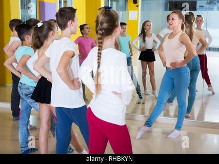 Young dance coach giving children dance class, showing movements in dance studio