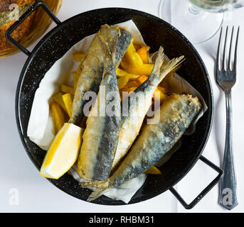 Delicious sardines in Andalusian marinade served with French fries and lemon - Stock Photo