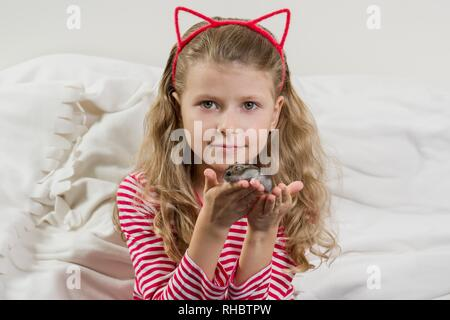 Girl child 7 years old blonde with long wavy hair holds in the hands of her beloved pet - hamster. Caring for a child about pet - Stock Photo
