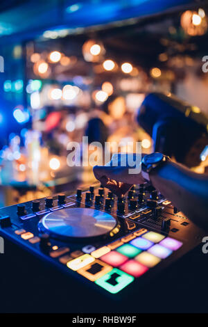 DJ plays live set and mixing music on turntable console at stage in the night club. Disc Jokey Hands on a sound mixer station at club party. DJ mixer - Stock Photo