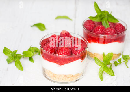 Homemade cheesecake with raspberries and mint in glasses - Stock Photo