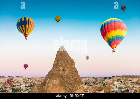 Colorful hot air balloons flying over at fairy chimneys in Nevsehir, Goreme, Cappadocia Turkey. Hot air balloon flight at spectacular Cappadocia Turke - Stock Photo