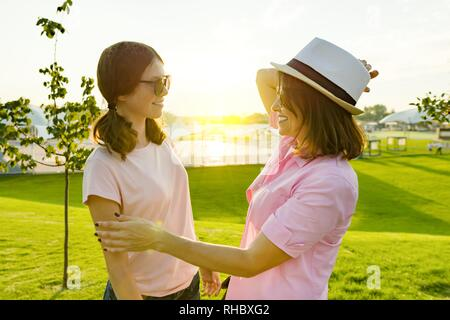 Communication of the parent and adolescent, teenage girl talking with mom. Background green lawn, recreation and entertainment zone. - Stock Photo