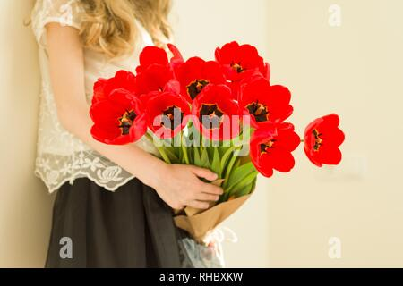 Child girl holding bouquet of red tulips flowers. Gift, surprise, spring family holiday. - Stock Photo