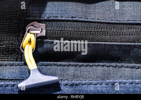 Close up on zipper of a travel bag with yellow cord and plastic on the end - Stock Photo