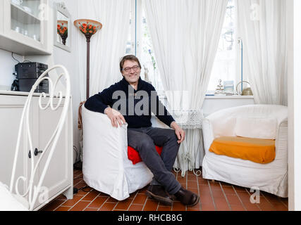 01 February 2019, Schleswig-Holstein, Lübeck: Holiday home owner Wolfgang Seitz sits in his apartment in a historic old building in the centre of Lübeck. Soon the picturesque gang houses in Lübeck will no longer be allowed to be rented to tourists. The homeowners want to sue against the usage ban. They threaten to sell their cottages as second homes to Scandinavians, for example. Photo: Markus Scholz/dpa - Stock Photo