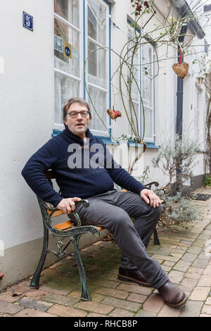 01 February 2019, Schleswig-Holstein, Lübeck: Holiday home owner Wolfgang Seitz sits in front of his apartment in a historic old building in the centre of Lübeck. Soon the picturesque gang houses in Lübeck will no longer be allowed to be rented to tourists. The homeowners want to sue against the usage ban. They threaten to sell their cottages as second homes to Scandinavians, for example. Photo: Markus Scholz/dpa - Stock Photo