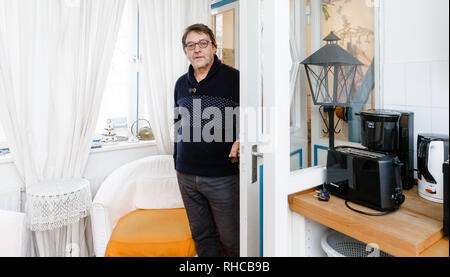 01 February 2019, Schleswig-Holstein, Lübeck: Holiday home owner Wolfgang Seitz stands in his apartment in a historic old building in the centre of Lübeck. Soon the picturesque gang houses in Lübeck will no longer be allowed to be rented to tourists. The homeowners want to sue against the usage ban. They threaten to sell their cottages as second homes to Scandinavians, for example. Photo: Markus Scholz/dpa - Stock Photo