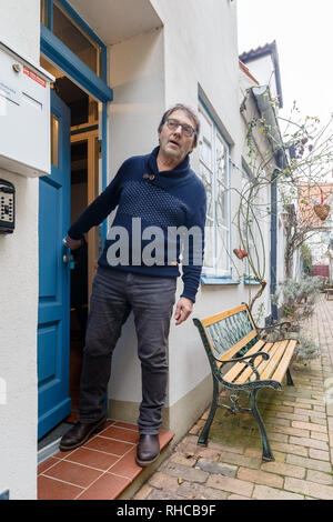 01 February 2019, Schleswig-Holstein, Lübeck: Holiday home owner Wolfgang Seitz stands in front of his apartment in a historic old building in the centre of Lübeck. Soon the picturesque gang houses in Lübeck will no longer be allowed to be rented to tourists. The homeowners want to sue against the usage ban. They threaten to sell their cottages as second homes to Scandinavians, for example. Photo: Markus Scholz/dpa - Stock Photo