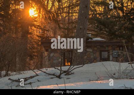 The rising sun illuminates a stone cabin in northern Wisconsin. - Stock Photo
