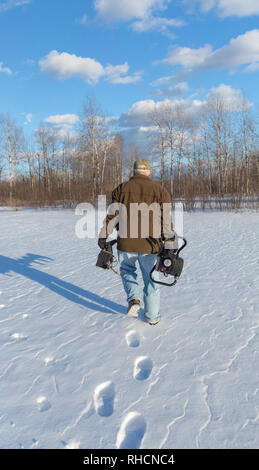 Ice fisherman carrying a fish locator in one hand and an ice auger in the other. - Stock Photo