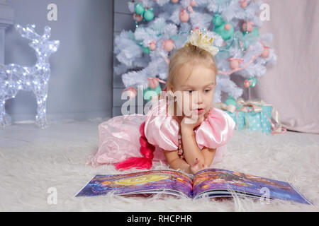 Portrait of cute european little blonde princess girl with crown in beautiful dress lying on the floor and reading book in decorated studio in christm - Stock Photo