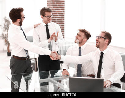 business colleagues shaking hands in the workplace - Stock Photo