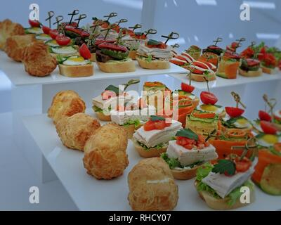Vegetable starters and meat snacks served on a plates close up - Stock Photo
