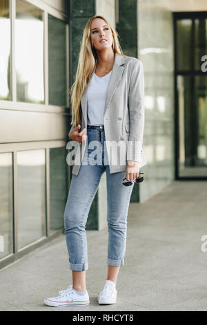 Beautiful young blonde woman in urban background. - Stock Photo