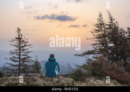 A young youth in headphones watches the sunrise in the mountains with a cup of tea, a sonception, a trip, a hike, a rest, solitude - Stock Photo