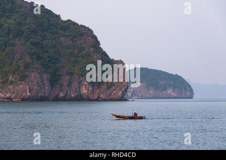 A local Vietnamese fisherman in his small wooden fishing boat with limestone islands in background, Ha Long Bay, Vietnam - Stock Photo