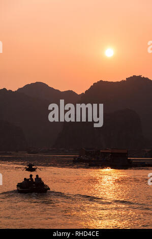 Locals in small wooden fishing boat and fishing village silhouetted amongst limestone karsts as the sun sets, Ha Long bay, Vietnam - Stock Photo