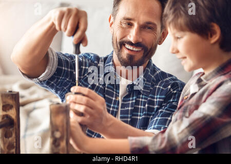Father and little son together at home standing at table dad screwing screw laughing happy looking at boy holding chair leg teamwork close-up - Stock Photo