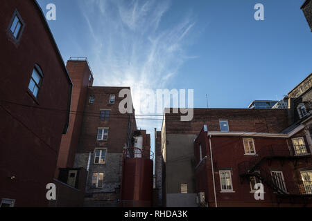 Backyard of some old, poor and dilapidated red brick buildings, of the vintage North American architectural style, in downtown Montreal, Quebec, Canad - Stock Photo