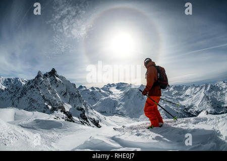 A male skier stands on the ridge between the ski resorts of Courchevel and Méribel in France with a sun halo caused by ice crystals in the air behind. - Stock Photo