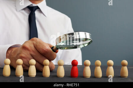 Recruiter looking through magnifying glass on candidates. Hiring and recruiting. - Stock Photo