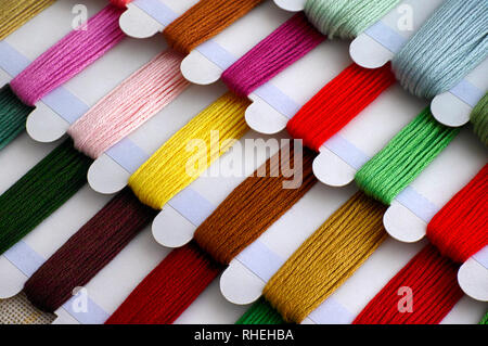 Colored embroidery threads on spools ready for cross stitch. Close-up.