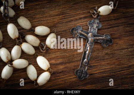 Catholic cross with a rosary on a wooden background