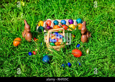Chocolate Easter bunnies, straw basket full of colourful eggs on green grass - Stock Photo