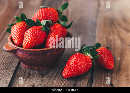 Bowl of fresh strawberries on the wooden table - Stock Photo