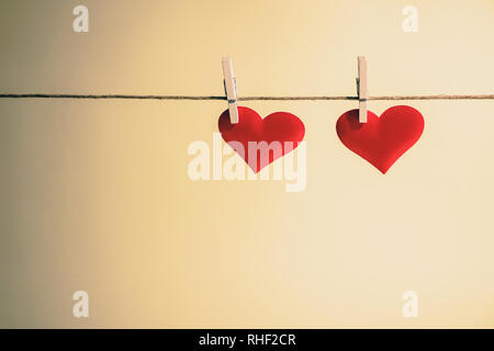 Two adorable red hearts side by side hanging from a string by wooden pegs. Romantic Valentine's Day with copy space. - Stock Photo